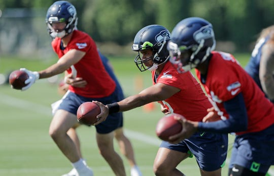 Seattle Seahawks quarterback Russell Wilson, center, drops back next to passes next to backup quarterbacks Paxton Lynch, left, and Geno Smith, right, during NFL football training camp, Monday, Aug. 5, 2019, in Renton, Wash.