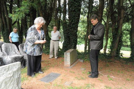 Former Montreat College librarian Sue Diehl stands over the grave of Helen Louise Dickinson, a librarian at the college in the early 20th century.