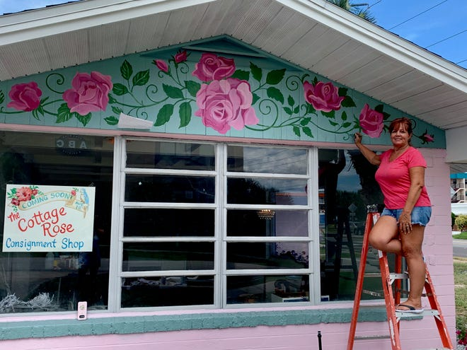 Key Largo artist Ginger Hill paints decorative roses on an exterior wall of Cottage Rose in Indialantic in this mid-July photo.