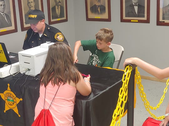 Ayden Gerber, 8, gets his photo and thumbprint taken on Aug. 5, 2019, at the Ross County Fair.
