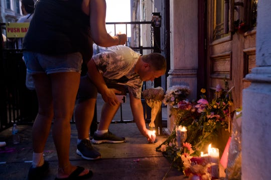 A person lays a candle outside Ned Pepper's Bar during a vigil for the victims of  a mass shooting in the Oregon District of Dayton, Ohio, on Sunday, Aug. 4, 2019.