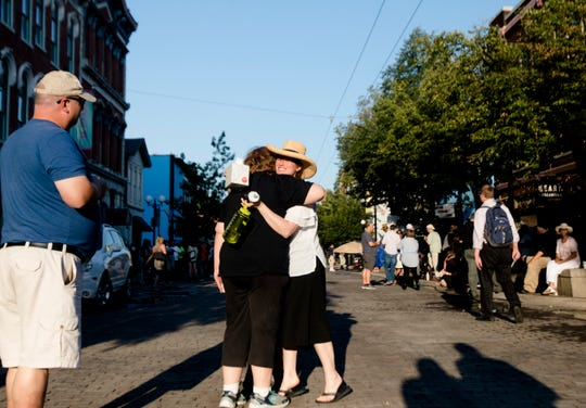 Anne Petratis, left, embraces Caitlin Cipolla-McCulloch in the middle of the 400 block of East Fifth Street before a vigil for the victims of a mass shooting in the Oregon District of Dayton, Ohio, on Sunday, Aug. 4, 2019.