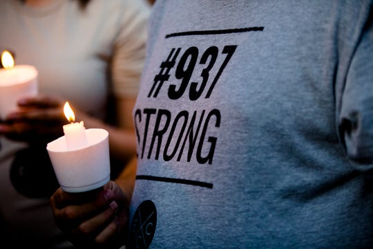A man holds a candle while wearing a 937 Strong shirt during a vigil held for the victims of  a mass shooting on the street, the 400 block of East 5th Street, where it happened in the Oregon District of Dayton, Ohio, on Sunday, Aug. 4, 2019.