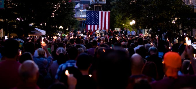 People look on during a vigil for the victims of  a mass shooting in the Oregon District of Dayton, Ohio, on Sunday, Aug. 4, 2019.