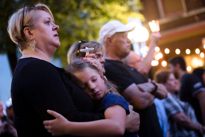 A woman embraces a child during a vigil for the victims of  a mass shooting in the Oregon District of Dayton, Ohio, on Sunday, Aug. 4, 2019.
