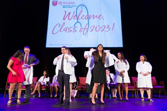 Members of the incoming class of Rutgers Robert Wood Johnson Medical School are coated by members of the faculty during the White Coat Ceremony.