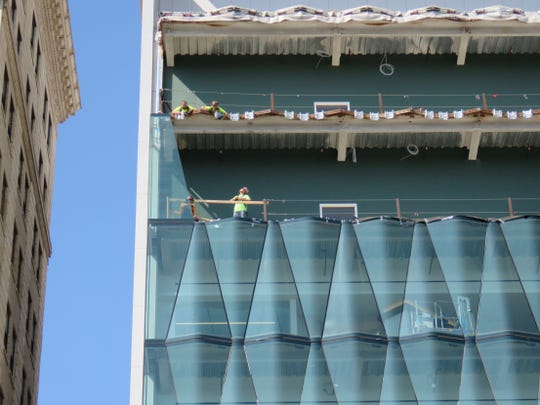 Workers install glass shaped like pizza slices along the top two floors of Little Caesars headquarters Monday, Aug. 5, 2019, on Woodward in downtown.