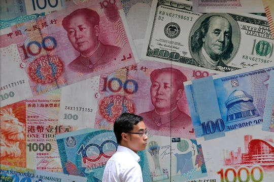 A man walks past a money exchange shop decorated with different banknotes at Central, a business district of Hong Kong.