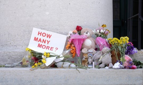 Candles, flowers and signs were left outside of the Ohio Statehouse in Columbus following mass shootings in El Paso, Texas., and Dayton, Ohio, on Monday, Aug. 5, 2019.