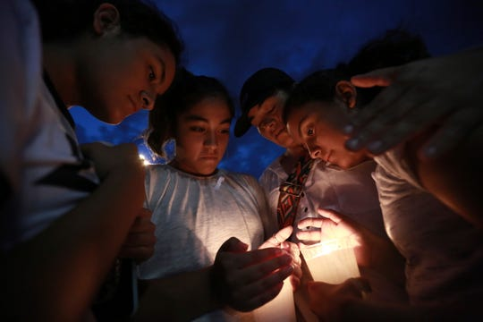 People gather in Juarez, Mexico, Saturday, Aug. 3, 2019, in a vigil for the 3 Mexican nationals who were killed in an El Paso shopping-complex shooting.