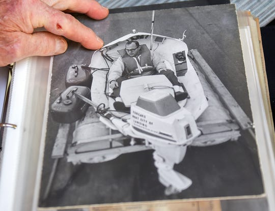 In this Monday, July 24, 2019 photo, Vic Jackson talks about his trip across Lake Michigan in a bathtub in 1969 at his home while looking at memorabilia from the trip in Okemos, Mich. Jackson tells his story in a new book. (Nick King/Lansing State Journal via AP)