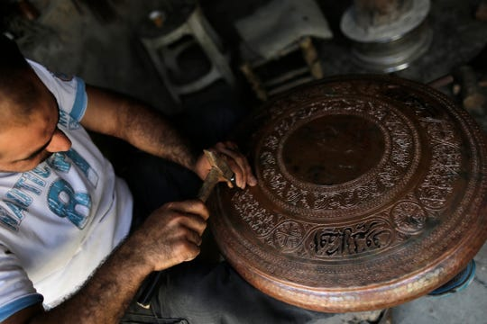 In this Sunday, July 28, 2019 photo, Ahmad Zuhdi Ghazoul works on a piece of copper on the newly renovated copper market in Aleppo, Syria.