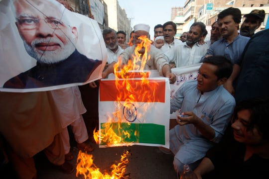 Pakistanis burn a representation of an Indian flag and a poster of Indian Prime Minster Narendra Modi during a protest to express support and solidarity with Indian Kashmiri people in their peaceful struggle for their right to self-determination, in Peshawar, Pakistan, Monday, Aug. 5, 2019.