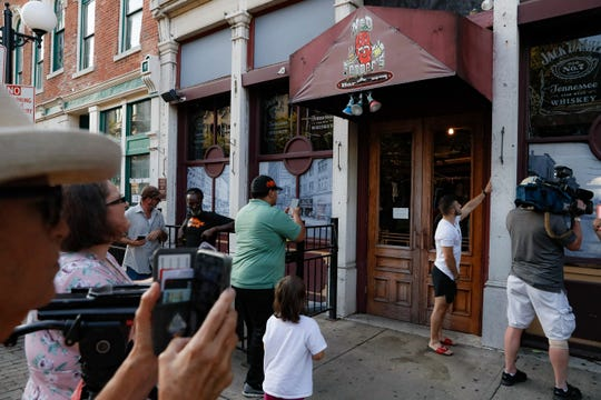 Mourners pause at the front of Ned Peppers bar while they gather at the scene of a mass shooting before a prayer vigil, Sunday, Aug. 4, 2019, in Dayton, Ohio.