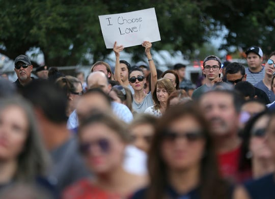 A message of hope is held up during the Hope Border Institute prayer vigil Sunday, Aug. 4, 2019 in El Paso, Texas, a day after a mass shooting at a Walmart store.