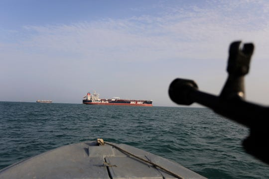 In this In this July 21, 2019 file photo, a speedboat of Iran's Revolutionary Guard trains a weapon toward the British-flagged oil tanker Stena Impero, which was seized in the Strait of Hormuz on July 19 by the Guard, in the Iranian port of Bandar Abbas.