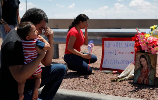 Dr. Julio Novoa, left, and Danielle Novoa, right, kneel beside a makeshift memorial with their 10-month-old son Ricard Novoa at the scene of the El Paso, Texas, shooting.