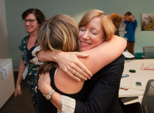 Newly promoted Detroit News Managing Editor Kelley Root receives a congratulatory hug from design writer Maureen Feighan after the announcement.