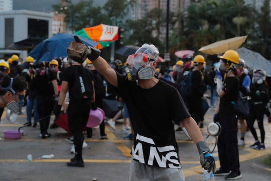 A protester holds a brick during confrontation with police in Hong Kong Monday, Aug. 5, 2019.