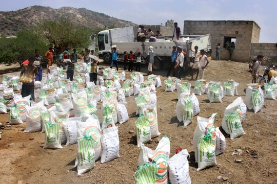 In this Sept. 23, 2018 file photo, men deliver aid donations from donors, in Aslam, Hajjah, Yemen.