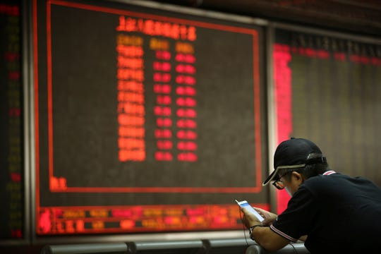 A Chinese investor uses his smartphone as he monitors stock prices at a brokerage house in Beijing, Friday.