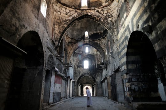 In this Saturday, July 27, 2019 photo, a Syrian man checks a market in the old city of Aleppo, Syria.
