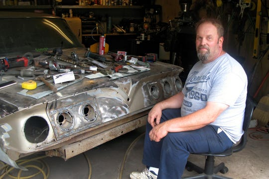 "Mike Lindstrom of Marquette Township poses next to his 1961 Impala that he is customizing in Marquette Township. ""I'm doing some customizing to it, putting '63-style Corvette taillights in it,"" Lindstrom said. He also is customizing the grill area and door handles, and plans a paint job: an emerald green ""Cadillac"" color with a white pearl gold roof."