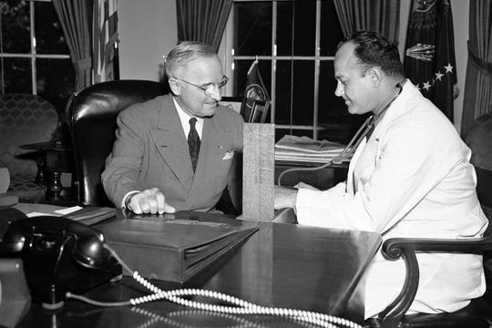 In this Sept. 3, 1949, file photo, Brigadier Gen. Wallace Harry Graham, right, personal physician of President Harry S. Truman checks his blood pressure in the president's office in Washington.