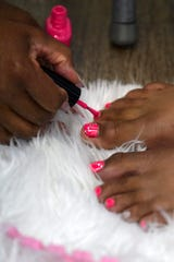 Volunteer DeAjiah Brodie touches up 12-year-old Sariyiah Lattimore's toe nail paint after it got smudged during a free hair and nail styling event at 9 Fruits Beauty Salon in Evansville, Ind., Monday morning, Aug. 5, 2019. The salon partnered with Jerald's Barbershop, located in the same building on Walnut Street, and youth mentoring group Young and Established to give kids free haircuts before going back to school this week.