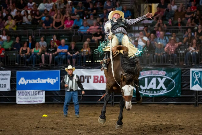 Saddle bronc rider Justin Hegwer holds onto Hi Flyer during the PRCA Rodeo on Sunday, Aug. 4, 2019, at the Budweiser Event Center in Loveland, Colo.