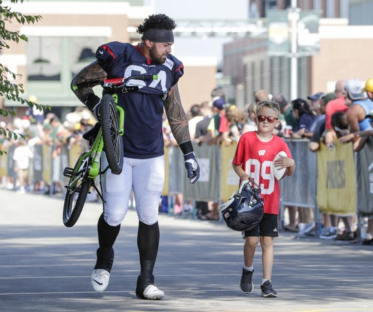 Texans guard Senio Kelemete (64) carries a bike to Clarke Hinkle Field for a joint training camp practice with the Green Bay Packers Monday, August 5, 2019, in Ashwaubenon, Wis.