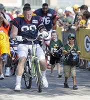 Texans defensive end J. J. Watt rides into to Clarke Hinkle Field for a joint training camp practice with the Green Bay Packers Monday, August 5, 2019, in Ashwaubenon, Wis.
