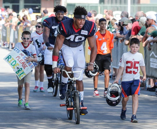 Texans outside linebacker Davin Bellamy (48) joins the Packers tradition of riding bikes to Clarke Hinkle Field for a joint training camp practice with the Green Bay Packers Monday, August 5, 2019, in Ashwaubenon, Wis.