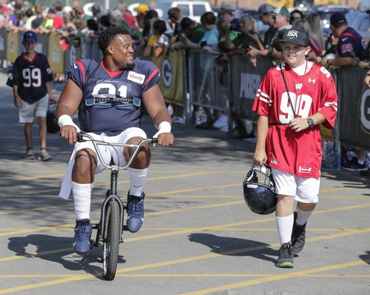 Texans defensive end Carlos Watkins (91) rides a bike to Clarke Hinkle Field for a joint training camp practice with the Green Bay Packers Monday, August 5, 2019, in Ashwaubenon, Wis.