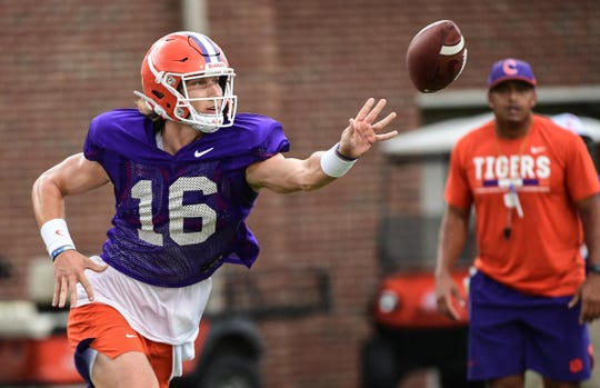 Clemson quarterback Trevor Lawrence (16) pitches a ball to a running back during practice at the Allen N. Reeves Football Complex Monday, August 5, 2019.