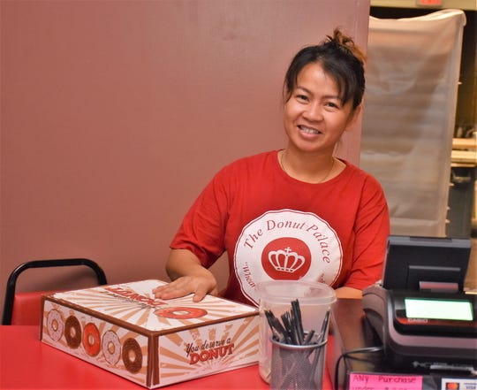 Rom Ouk, owner of the Donut Palace, boxes up a dozen freshly made donuts for a customer.