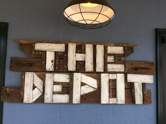 A sign made from repurposed wood adorns the front of Mark Gilleran's shop.