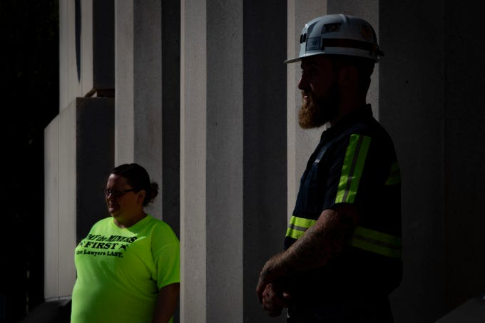 Former Blackjewel miner Austin Watts, right, stands outside the Robert C. Byrd Federal Courthouse in Charleston, West Virginia. Watts and approximately 50 former Blackjewel miners made the four hour drive from Harlan County to attend the Blackjewel coal company bankruptcy court hearing Monday. Aug. 5, 2019
