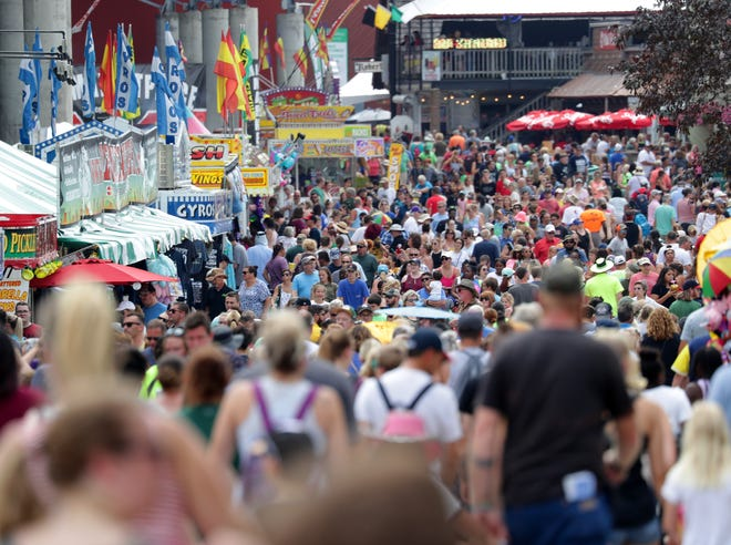 People walk near the stadium and food booths at the Wisconsin State Fair.