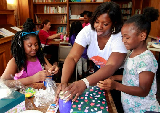 "LaTasha Langdon (center) of Divine Destinies helps Princess Larry (right), 9, and Ericka Day-Griffin, 10, with their jars of positive affirmations and photo boxes for a class called ""Creative arts: expression and esteem"" at City On A Hill."