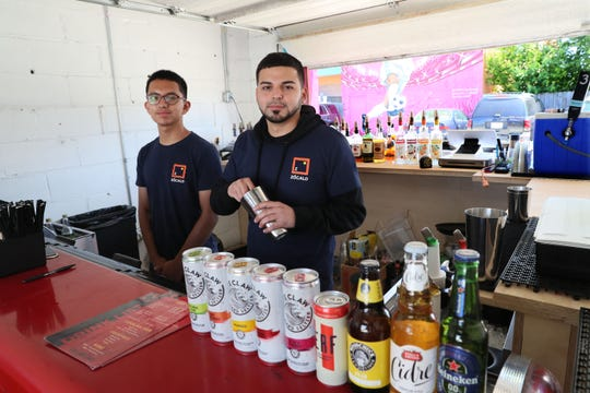 Bartenders Kenneth Romo (left) and Cesar Ramirez serve drinks in the open-air bar at the food truck park.