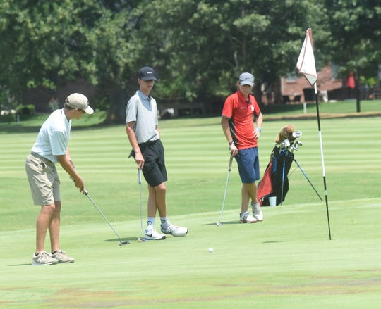 Mountain Home's Gaige Chaney (left) watches his putt go in the hole on Monday at Big Creek.