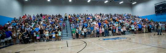 The crowd stands for the singing of the National Anthem at the Rocky Fork Elementary School open house and dedication Sunday.