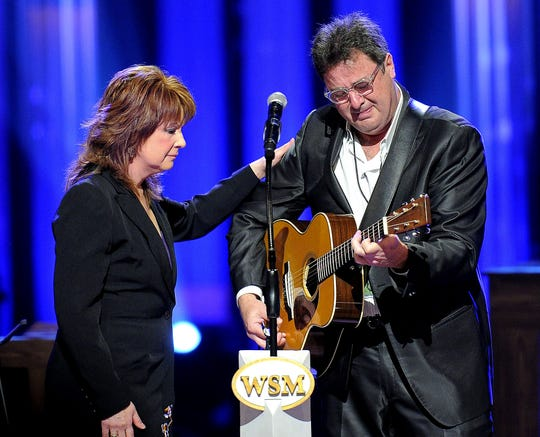 "Patty Loveless comforts a tearful Vince Gill as they sing his ""Go Rest High on That Mountain"" during the May 2, 2013, memorial service for George Jones at the Grand Ole Opry House."