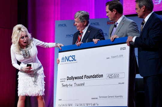 Dolly Parton receives a check for $25,000 for the Dollywood Foundation at the NCSL Legislative Summit at Music City Center. Monday, Aug. 5, 2019, in Nashville, Tenn.