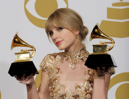"Taylor Swift poses backstage with the awards for best country song and best country solo performance for ""Mean"" during the 54th annual Grammy Awards show Feb. 12, 2012 in Los Angeles."