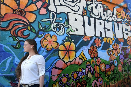 "Ashlee Sellars stands next to one of her favorite mural by artist Omari Booker which says, ""They tried to bury us. little did they know we were seeds."" Sellars was sentenced to 25 years in prison on a crime she was a bystander to at 17 years old. She was released in 2017 and now works with a Nashville nonprofit aimed at ""restorative justice"" and bringing youth in the criminal justice system to places of healing with the people they hurt in the crimes they committed."