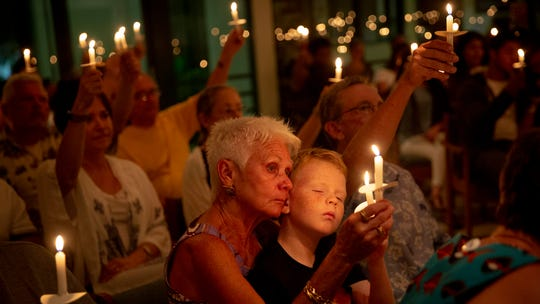 Ellen Vaughn holds her grandson Liam Owens, 9, during a vigil for migrants in detention facilities held at the Unitarian Universalist Congregation of Greater Naples on Friday, July 12, 2019. The vigil was one of many international events that made up Lights for Liberty: A Vigil to End Human Concentration Camps.