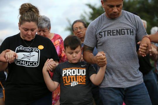 Una familia reza tomada de la mano, en memoria de las víctimas del tiroteo en El Paso, Texas.