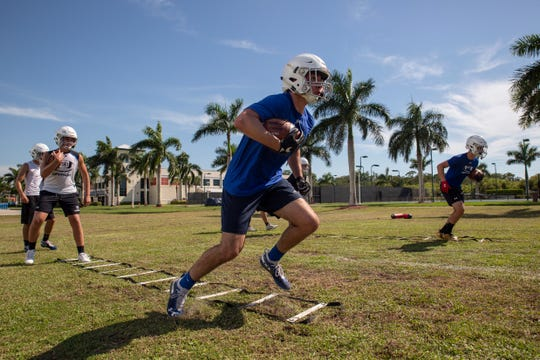 Football players run drills during the Community School of Naples's first football practice of the fall season in North Naples on Tuesday, July 30, 2019.